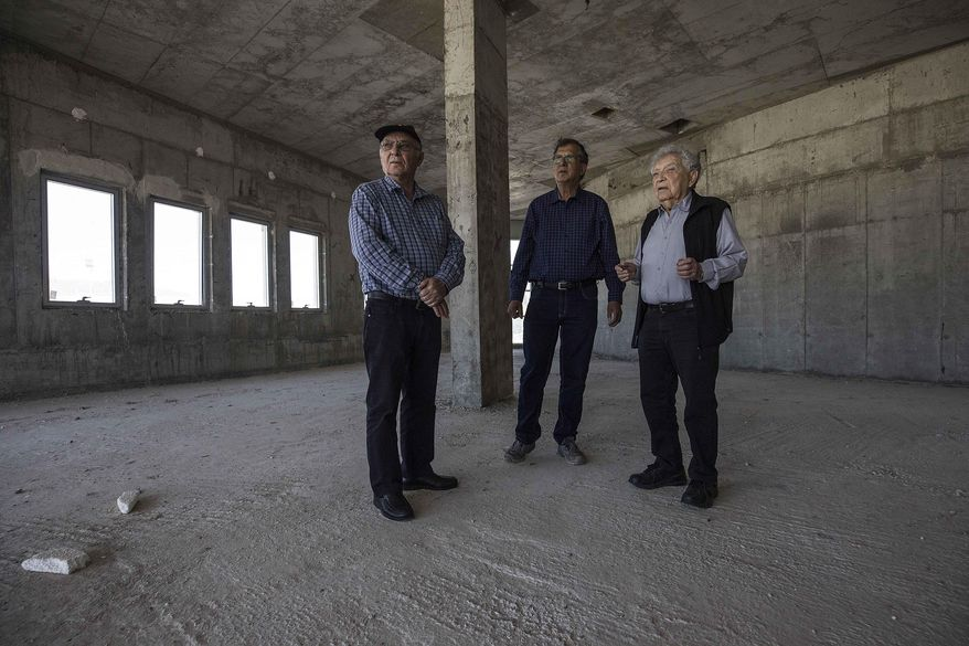 In this Tuesday, April 18, 2017 photo, Jewish World War II veterans Chaim Erez, left, Zvi Kan-Tor, center, and Yitzhak Arad stand during an interview with The Associated Press inside the unfinished museum honoring Jewish World War II veterans, in Latrun, Israel. Two years after Israel's Prime Minister Benjamin Netanyahu vowed to complete the establishment of a museum honoring Jewish World War II veterans, funds have dried up and an abandoned construction site is all that remains of the project. The story of the 1.5 million Jews who fought the Nazis -- and the 250,000 who died in battle -- has long been lost in Israel amid the larger tragedy of the Holocaust. (AP Photo/Tsafrir Abayov)
