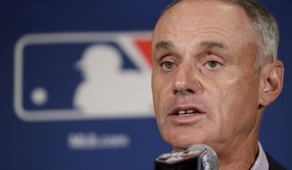 """FILE- In this Feb. 21, 2017, file photo, Major League Baseball Commissioner Rob Manfred answers questions at a news conference in Phoenix. The Los Angeles Dodgers and New York Yankees are cutting payroll and their luxury tax bills, just as Bryce Harper, Manny Machado and perhaps Clayton Kershaw near the free-agent market after the 2018 season. """"What the market produces is what the market's going to produce,"""" Manfred said.  (AP Photo/Morry Gash, File)"""