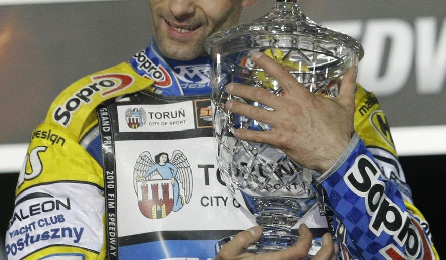 FILE - In this file photo taken in Prague, Czech Republic, May 22, 2010, speedway champion Tomasz Gollob of Poland poses with the trophy for winner of the World Speedway Grand Prix. Doctors in Poland say Monday, April 24, 2017 he is in hospital in induced coma and on respirator following an accident in which he injured his spine and chest. (AP Photo/Petr David Josek, file )