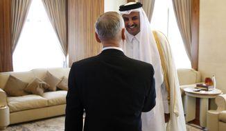 Qatar's Emir Sheikh Tamim Bin Hamad Al-Thani, right, greets U.S. Defense Secretary Jim Mattis at his residence, the Sea Palace, in Doha, Qatar, Saturday, April 22, 2017. (Jonathan Ernst/Pool Photo via AP)