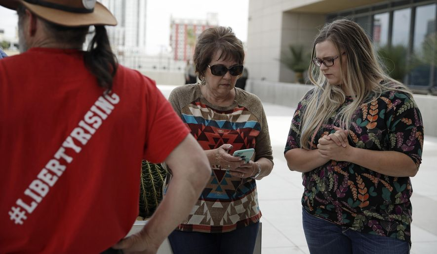 Carol Bundy, center, wife of Nevada rancher Cliven Bundy, looks at her phone beside Bailey Logue, daughter of Cliven Bundy, while waiting for a verdict outside of the federal courthouse, Monday, April 24, 2017, in Las Vegas. A jury found two men guilty of federal charges Monday in an armed standoff that stopped federal agents from rounding up cattle near Cliven Bundy's Nevada ranch in 2014. Jurors said they were deadlocked on charges against four other men, and the judge told them to keep deliberating. (AP Photo/John Locher)