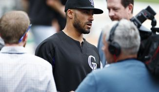 Colorado Rockies first baseman Ian Desmond talks to reporters after taking batting practice for the first time since his hand was broken by a pitch during spring training as the Rockies prepare to face the Washington Nationals in a baseball game Monday, April 24, 2017, in Denver. (AP Photo/David Zalubowski)