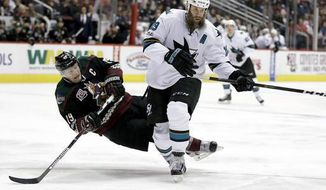 FILE - In this Feb. 18, 2017, file photo, San Jose Sharks center Joe Thornton, right, knocks the puck away from Arizona Coyotes right wing Shane Doan during the third period of an NHL hockey game in Glendale, Ariz. Thornton will undergo surgery to repair torn ligaments in his left knee before becoming a potential free agent this summer. (AP Photo/Chris Carlson, File)