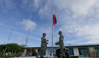 FILE - In this Friday, April 21, 2017, file photo, Philippine troopers raise the Philippine flag during a ceremony upon the arrival of Philippine Defense Secretray Delfin Lorenzana, Armed Forces Chief Gen. Eduardo Ano and other officials on the Philippine-claimed island of Pag-asa, also know as Thitu, off the disputed Spratlys chain of islands in the South China Sea. Lorenzana and Ano flew to the island in the South China Sea, drawing a protest from China, which also claims the remote territory. (AP Photo/Bullit Marquez, File)