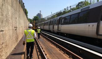 In this photo taken July 25, 2016, Metro general manager Paul Wiedefeld walks along a track that's been closed for maintenance while an orange line train rolls along the other track in northern Virginia.  (AP Photo/Ben Nuckols) **FILE**