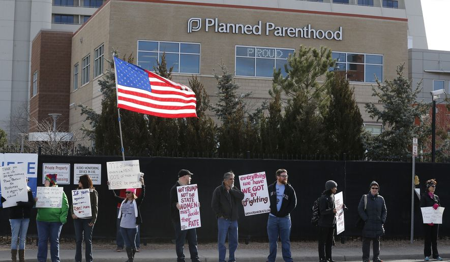 Pro-choice counter-protesters hold signs supporting a woman's right to choose abortion, as nearby anti-abortion activists held a rally in front of Planned Parenthood of the Rocky Mountains in Denver on Feb. 11, 2017. (Associated Press) **FILE**