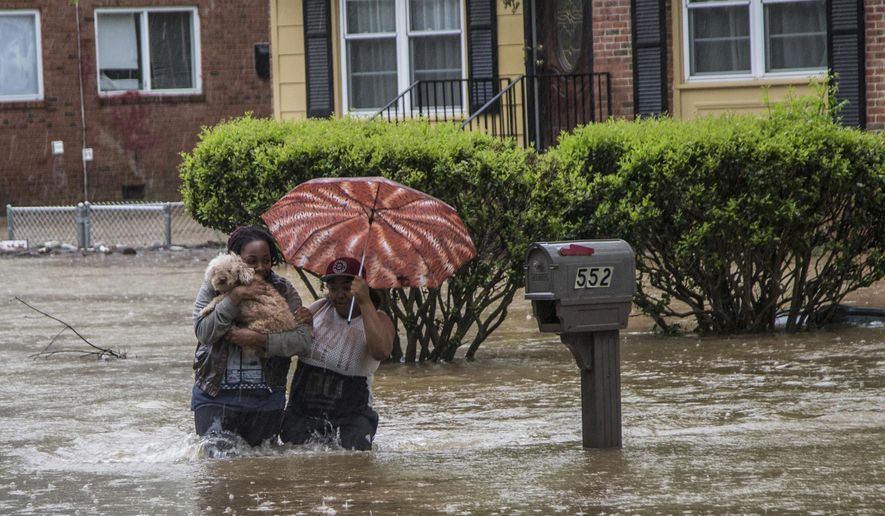 Nautica Jackson, left, and Aniya Ruffin walk through floodwaters with their dog as water threatened to enter their home in Raleigh, N.C. Tuesday, April 25, 2017.  The National Weather Service had flood watches and warnings in effect in the eastern half of the state Tuesday morning after storms dumped several inches of rain in the Raleigh area. (Travis Long/The News & Observer via AP)