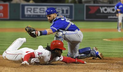 Los Angeles Angels' Cameron Maybin, left, scores on fielder's choice ball hit by David Hernandez as Toronto Blue Jays catcher Russell Martin makes a late tag during the fifth inning of a baseball game, Monday, April 24, 2017, in Anaheim, Calif. (AP Photo/Mark J. Terrill)
