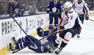Toronto Maple Leafs center Mitch Marner (16) is knocked to the ice by Washington Capitals defenseman Matt Niskanen (2) during the second period of Game 6 of an NHL hockey Stanley Cup first-round playoff series in Toronto on Sunday, April 23, 2017. (Nathan Denette/The Canadian Press via AP)
