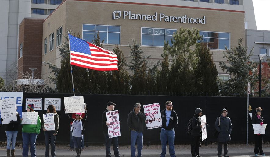 FILE - In this Feb. 11, 2017 file photo, pro-choice counter-protesters hold signs supporting a woman's right to choose abortion, as nearby anti-abortion activists held a rally in front of Planned Parenthood of the Rocky Mountains, in Denver. April 25, 2017, marks the 50th anniversary of a groundbreaking bill signed into law by a Republican governor that significantly loosened 1960s restrictions on legal abortions. That made Colorado the first U.S. state to do so, six years before the U.S. Supreme Court legalized abortion nationwide. (AP Photo/Brennan Linsley, File)