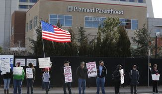 In this Feb. 11, 2017, photo, pro-choice counter-protesters hold signs supporting a woman's right to choose abortion, as nearby anti-abortion activists held a rally in front of Planned Parenthood of the Rocky Mountains, in Denver. April 25, 2017, marks the 50th anniversary of a groundbreaking bill signed into law by a Republican governor that significantly loosened 1960s restrictions on legal abortions. That made Colorado the first U.S. state to do so, six years before the U.S. Supreme Court legalized abortion nationwide. (AP Photo/Brennan Linsley) **FILE**
