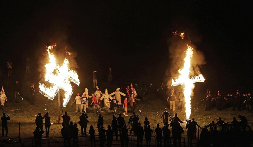"In this April 23, 2016 file photo, members of the Ku Klux Klan participate in cross and swastika burnings after a ""white pride"" rally in rural Paulding County near Cedar Town, Ga. (AP Photo/Mike Stewart)"