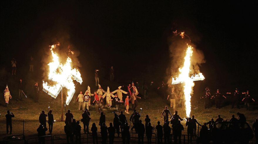 """In this April 23, 2016 file photo, members of the Ku Klux Klan participate in cross and swastika burnings after a """"white pride"""" rally in rural Paulding County near Cedar Town, Ga. (AP Photo/Mike Stewart)"""