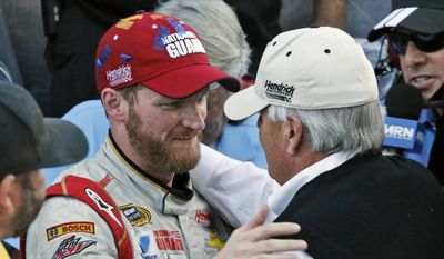In this Oct. 26, 2014, file photo, Dale Earnhardt Jr. celebrates winning the NASCAR Sprint Cup Series auto race with team owner Rick Hendrick, front right, in Victory Lane at Martinsville Speedway in Martinsville, Va. Hendrick Motorsports says Dale Earnhardt Jr. will retire at the end of this season. (AP Photo/Steve Helber, File)