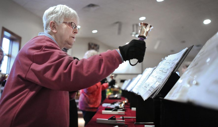 In an April 19, 2017 photo, Evie Miller hits her note while practicing  with the Milton United Methodist Church handbell Choir for an upcoming concert in Milton, Wis. The handbell choir is one of three that will perform at the fifth annual community handbell concert at Milton's Seventh Day Baptist Church on Sunday, April 30, that's open to the public. (Anthony Wahl/The Janesville Gazette via AP)
