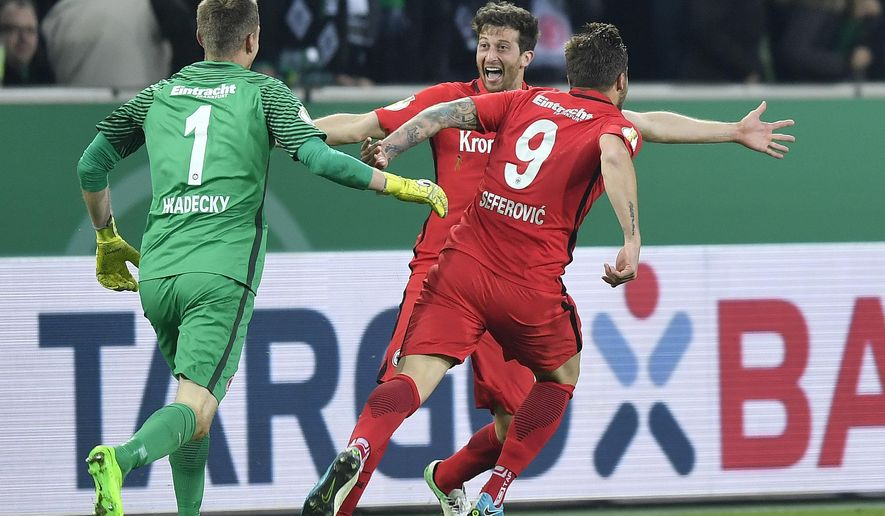 Frankfurt goalkeeper Lukas Hradecky, David Abraham, and Haris Seferovic, from left, celebrate after the final penalty of the German Soccer Cup semifinal match between Borussia Moenchengladbach and Eintracht Frankfurt in Moenchengladbach, Germany, Tuesday, April 25, 2017. Borussia was defeated by Frankfurt with 6-7 after penalties. (AP Photo/Martin Meissner)
