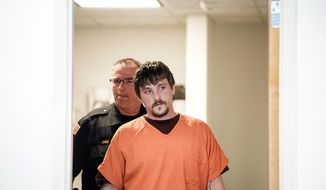 Joseph Jakubowski is escorted into a room at the Rock County Courthouse for his preliminary hearing Tuesday, April 25, 2017, in Janesville, Wis.  Prosecutors say Jakubowski mailed a rambling manifesto to President Donald Trump then stole 18 firearms from a store in Janesville on April 4. He was arrested 10 days later while camping on private property in southwestern Wisconsin, about 140 miles from Janesville. Jakubowski pleaded not guilty to state charges later Tuesday. (Angela Major/The Janesville Gazette via AP)