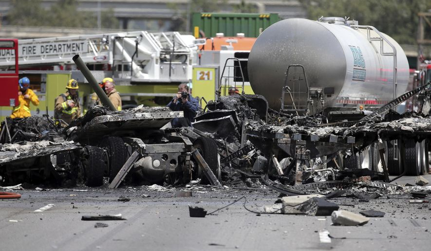Investigators view the wreckage after a fiery collision of two big trucks and several smaller vehicles killed one person and injured several others while triggering a massive traffic jam on Interstate 5 just north of downtown Los Angeles Tuesday, April 25, 2017.  (AP Photo/Reed Saxon)