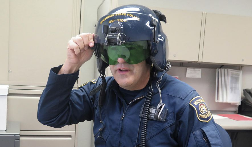 In a March 14, 2017 photo, Michigan State Police pilot Jerry King, shows a anti-laser shield in his office at a state police facility at Capital Region International Airport, in Lansing, Mich. Pilots use the anti-laser shield on their helmet when they are trying to pinpoint the source of a laser that is being shined at them or other aircraft. Michigan is poised to join a growing list of states and enact its own stiff law that criminalizes increasingly frequent laser attacks that are endangering pilots and their passengers. (AP Photo/David Eggert)