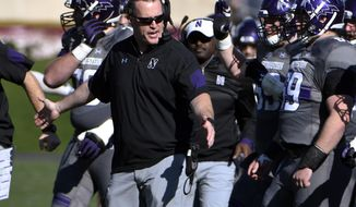FILE - In this Nov. 5, 2016, file photo, Northwestern coach Pat Fitzgerald greets his team after a defensive stop against Wisconsin during an NCAA college football game in Evanston, Ill. Northwestern has agreed to a new contract with Fitzgerald that runs through the 2026 season, according to two people with direct knowledge of the deal. The people spoke on condition of anonymity Monday, April 24, 2017, because Northwestern planned to make a formal announcement on Tuesday. (AP Photo/David Banks, File)