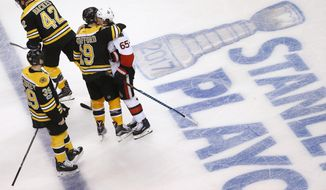 Boston Bruins' Drew Stafford (19) hugs Ottawa Senators' Erik Karlsson (65), of Sweden, after the Senators defeated the Bruins 3-2 during overtime in game six of a first-round NHL hockey Stanley Cup playoff series, Sunday, April 23, 2017, in Boston. (AP Photo/Michael Dwyer)