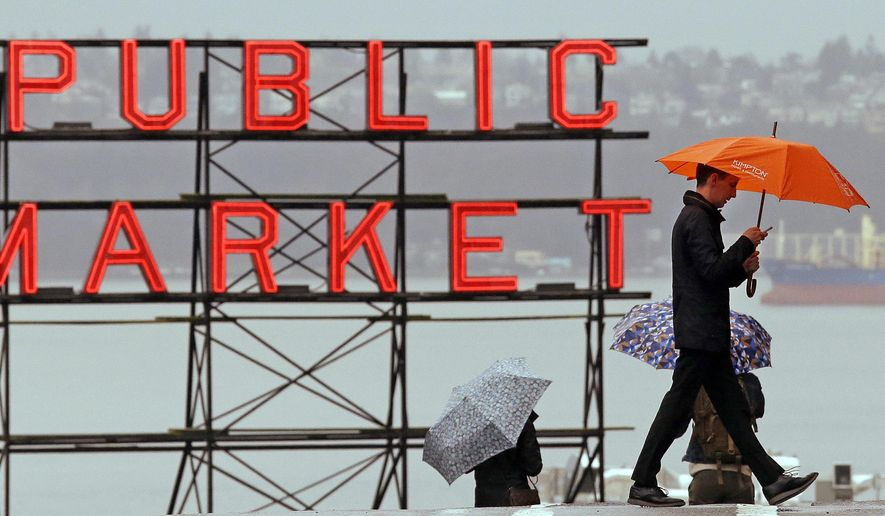 FILE - In this Jan. 18, 2017, file photo, pedestrians huddle under umbrellas as they walk past the Pike Place Market and in view of Elliot Bay, behind, in Seattle. The National Weather Service says the city has measured 44.67 inches of rain in the city between October 2016 and so far in April. That makes it the wettest such period since records began in 1895. Meteorologist Mike McFarland in the agency's Seattle office says it's the second year in the row that the city had topped the rainfall record for that 7-month period. (AP Photo/Elaine Thompson, File)