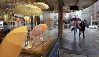 FILE - In This Jan. 18, 2017 file photo pedestrians under umbrellas pass a vintage umbrella shop in downtown Seattle. The National Weather Service says the city has measured 44.67 inches of rain in the city between October and April. That makes it the wettest such period since records began in 1895. With several days left in the month, the record will likely be padded some more. (AP Photo/Elaine Thompson,File)