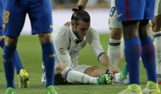 Real Madrid's Gareth Bale holds his leg after getting injured during a Spanish La Liga soccer match between Real Madrid and Barcelona, dubbed 'el clasico', at the Santiago Bernabeu stadium in Madrid, Spain, Sunday, April 23, 2017. (AP Photo/Daniel Ochoa de Olza)