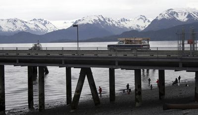 File - In this May 24, 2015 file photo, a vehicle drives on a pier to be loaded onto an Alaska state ferry while people fish underneath the pier in Homer, Alaska. Three leaders of the Alaska fishing community who wanted to promote inclusivity are fighting efforts to recall them from office. The recall election targeting three Homer City Council members is pegged to resolutions supporting the Standing Rock Sioux Tribe in its fight over a pipeline and aimed at promoting inclusivity in Homer following President Donald Trump's election. (AP Photo/Mark Thiessen, File)