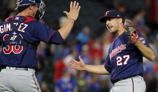 Minnesota Twins catcher Chris Gimenez (38) and relief pitcher Brandon Kintzler (27) celebrate after the final out of the ninth inning of a baseball game against the Texas Rangers in Arlington, Texas, Monday April 24, 2017. The Twins won 3-2. (AP Photo/Tony Gutierrez)