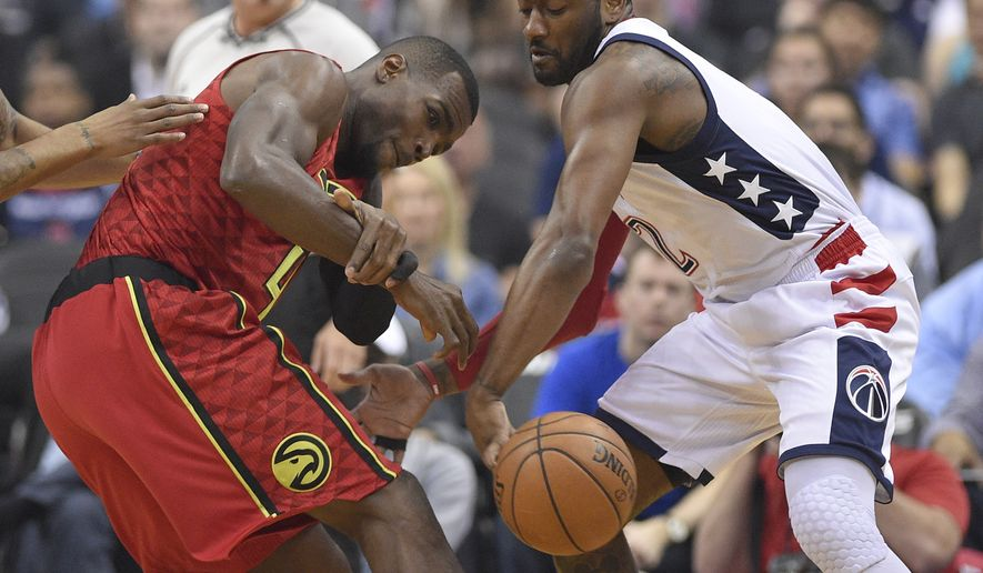 Washington Wizards guard John Wall (2) steals the ball away from Atlanta Hawks forward Paul Millsap, left, during the first half in Game 5 of a first-round NBA basketball playoff series, Wednesday, April 26, 2017, in Washington. (AP Photo/Nick Wass)