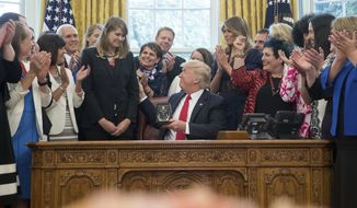 President Donald Trump, accompanied by Vice President Mike Pence, third from left, and first lady Melania Trump, center right, as he presents the 2017 National Teacher of the Year award to Codman Academy 9th grade humanities teacher Sydney Chaffee of Dorchester, Mass., center left, during a ceremony in the Oval Office at the White House in Washington, Wednesday, April 26, 2017. (AP Photo/Andrew Harnik)