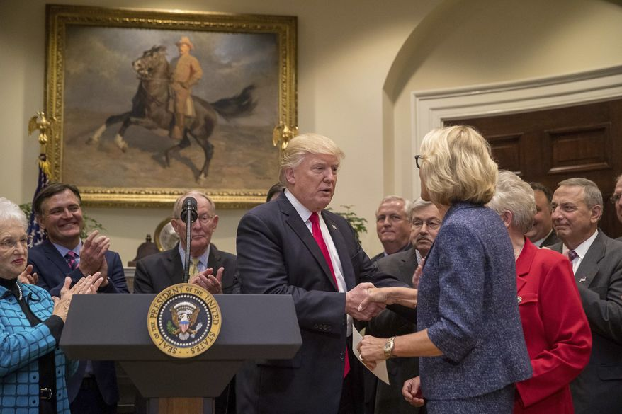 President Donald Trump greets Education Secretary Betsy DeVos before signing the Education Federalism Executive Order, Wednesday, April 26, 2017, in the Roosevelt Room of the White House in Washington. (AP Photo/Andrew Harnik)