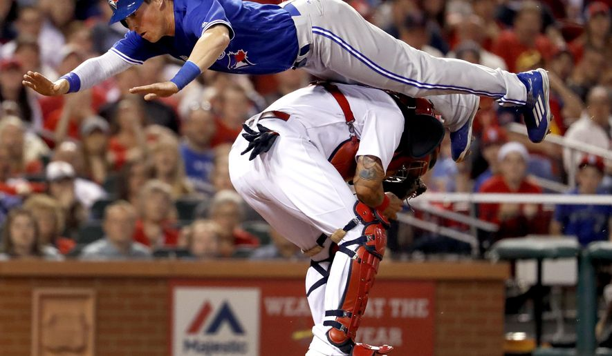 Toronto Blue Jays' Chris Coghlan leaps over St. Louis Cardinals catcher Yadier Molina to score during the seventh inning of a baseball game Tuesday, April 25, 2017, in St. Louis. (AP Photo/Jeff Roberson)