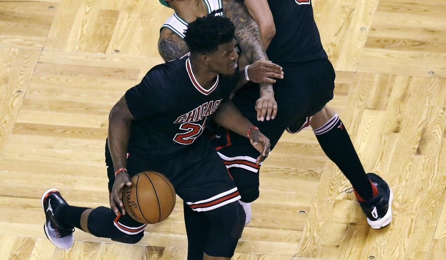 Chicago Bulls center Robin Lopez (8) fouls Boston Celtics guard Isaiah Thomas, center, who was covering forward Jimmy Butler (21) during the first quarter in Game 5 of a first-round NBA basketball playoff series in Boston, Wednesday, April 26, 2017. (AP Photo/Charles Krupa)