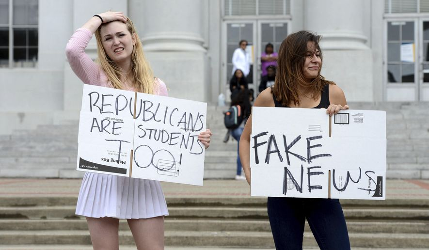 Ashton Whitty, left, 21, and Hailey Carlson, right, 24, University of California, Berkeley students, make their feelings known during a press conference held by the Berkeley College Republicans in Sproul Plaza on the Cal campus in Berkeley, Calif., on Wednesday, April 26, 2017. The event was held to discuss the cancellation of speaker Ann Coulter's appearance on campus. (Dan Honda/East Bay Times via AP)