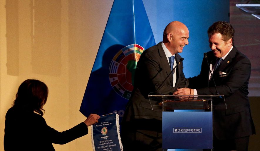 FIFA President Gianni Infantino, left, shakes hand with Alejandro Dominguez, right, Conmebol President during the 67 ordinary and extraordinary South American Football Confederation, CONMEBOL, congress in Santiago, Chile, Wednesday, April 26, 2017. (AP Photo/Esteban Felix)