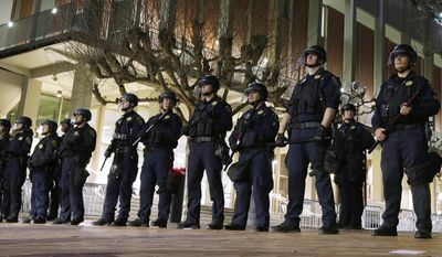 In this Feb. 1, 2017, file photo, University of California, Berkeley police guard the building where Breitbart News editor Milo Yiannopoulos was to speak in Berkeley, Calif. UC Berkeley police took a hands-off approach to protesters on the campus when violent rioters overtook a largely peaceful protest against a controversial speaker. After a series of protests around the country, some institutions are rethinking their security and tactics in an age of growing political polarization. (AP Photo/Ben Margot, File)