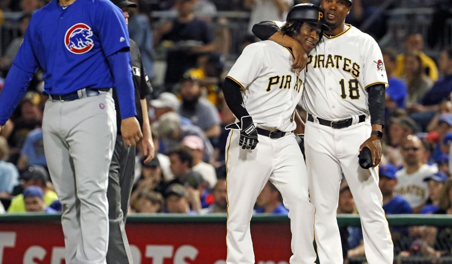 Pittsburgh Pirates' Gift Ngoepe, a native of South Africa, and the first baseball player from the continent of Africa to play in the Major Leagues, second from right, celebrates with first base coach Kimera Bartee (18) after getting a single off Chicago Cubs starting pitcher Jon Lester in his first Major League at-bat in the fourth inning of a baseball game in Pittsburgh, Wednesday, April 26, 2017. (AP Photo/Gene J. Puskar)