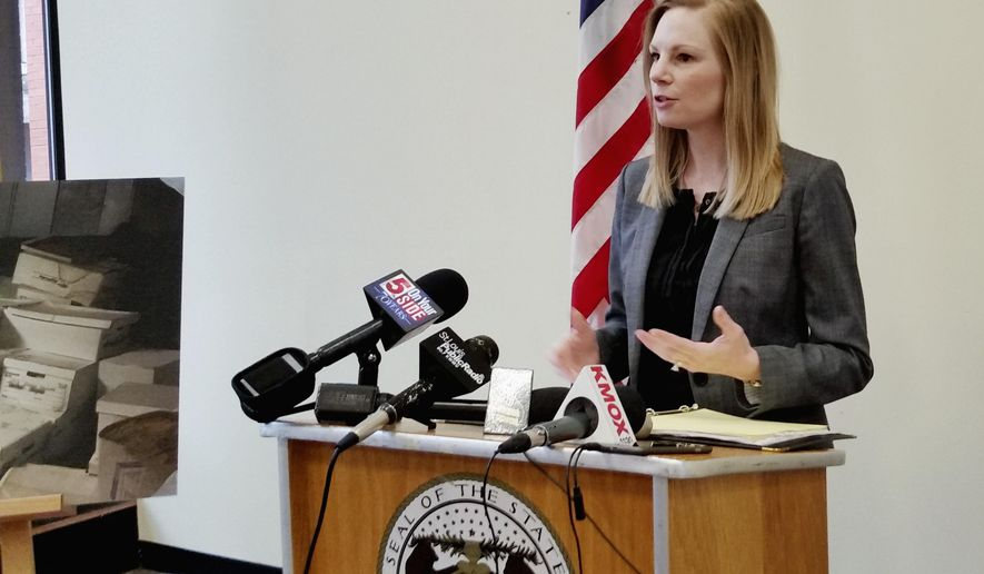 """Missouri Auditor Nicole Galloway stands next to a photo of mold-damaged files from the Ferguson municipal court during a news conference Wednesday, April 26, 2017, in St. Louis, where she discussed an audit that gave a poor rating to the court. The audit launched in the wake of unrest following the 2014 fatal police shooting of Michael Brown in Ferguson, Mo. found the city's court system """"in disarray"""" and disorganized, according to Galloway. (AP Photo/Jim Salter)"""