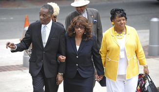 Bishop Rudolph W. McKissick, Sr., left, escorts former Congresswoman Corrine Brown to the Bryan Simpson Federal Courthouse in Jacksonville, Fla,., Wednesday, April 26, 2017, for opening arguments in her trial. Brown was indicted in July on 22 counts involving conspiracy, mail and wire fraud, filing false tax returns and hiding income. (Bruce Lipsky/The Florida Times-Union via AP)