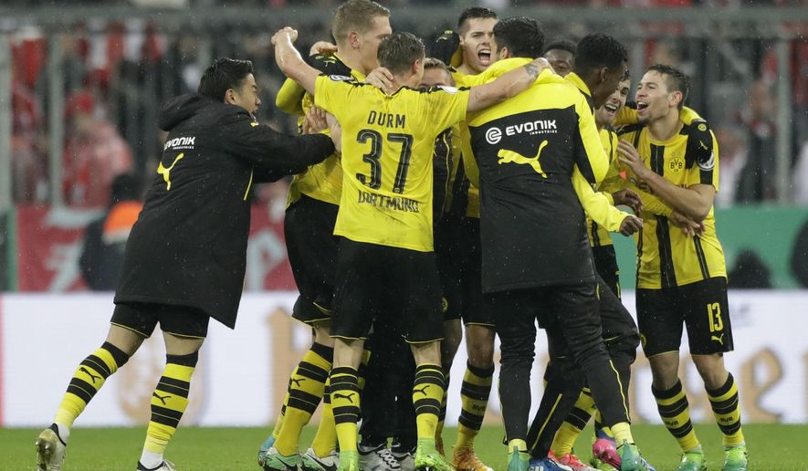 Dortmunds players celebrate after defeating Bayern Munich at the German Soccer Cup semifinal match between FC Bayern Munich and Borussia Dortmund at the Allianz Arena stadium in Munich, Germany, Wednesday, April 26, 2017. (AP Photo/Matthias Schrader)