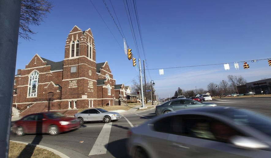 In this Feb. 10, 2015 photo, cars speed past the St. John United Church of Christ in Cumberland, Ind. Supporters of a historic church that has served as the gateway to a central Indiana community for more than a century are trying to raise more than $38,000 in just over a week to save it from demolition. (Kelly Wilkinson/The Indianapolis Star via AP)