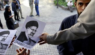 A supporter hands out pictures of Iranian cleric Ebrahim Raisi, a conservative presidential candidate in the upcoming election, at a campaign rally in Tehran, Iran, Wednesday, April 26, 2017. (AP Photo/Ebrahim Noroozi)