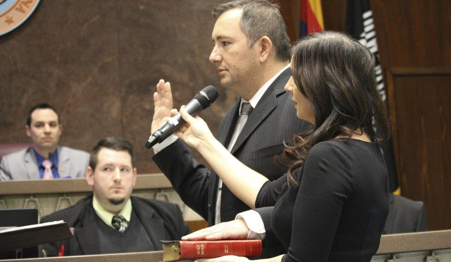 Peoria real estate broker and former city councilman, Ben Toma is sworn in as a member of the Arizona House of Representatives in Phoenix, Ariz., on Wednesday, April 26, 2017. His wife, Ana Toma, right, holds the Bible. Toma was picked from three nominees by the county Board of Supervisors to replace Republican Rep. Phil Lovas, who resigned to take a job with the Trump Administration. (AP Photo/Bob Christie)