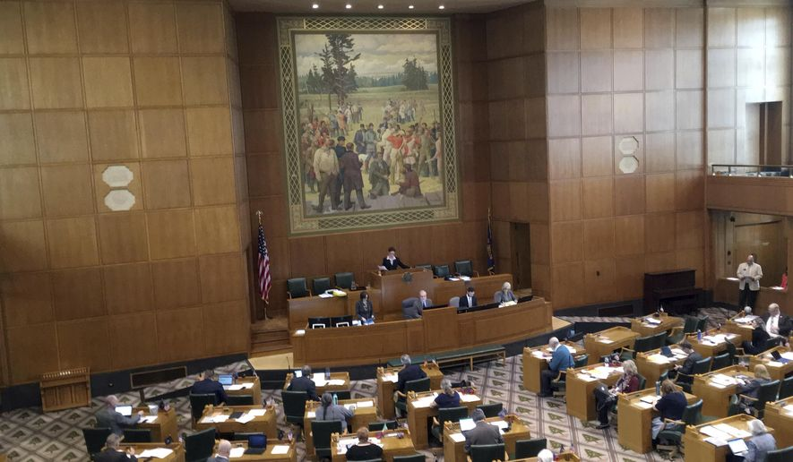 Lawmakers in Oregon's House of Representatives sit in session in Salem, Ore., Wednesday, April 26, 2017, after passing a bill that would require public universities and community colleges to respect people from all cultures, races and sexual orientations. Rep. Janelle Bynum, the only African-American in the House, referred to Oregon's original Constitution that prohibited black people from residing in the territory and said she was reminded of that by the huge mural of white settlers on the wall. (AP Photo/Andrew Selsky)