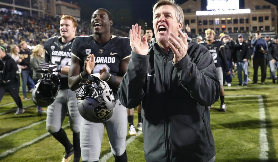 FILE - In this Nov. 19, 2016, file photo, Colorado coach Mike MacIntyre sings the school song with players after the team's 38-24 win over Washington State in an NCAA college football game in Boulder, Colo. The Buffaloes were one of 2016's best turnaround teams, winning the Pac-12 South after years of floundering. Mike MacIntyre won AP coach of the year for righting a ship that had long been listing. A major part of the turnaround was a much improved defense. Not only does CU have to replace eight defensive starters, including several NFL-caliber players, but coordinator Jim Leavitt left for Oregon, too. (AP Photo/David Zalubowski, File)