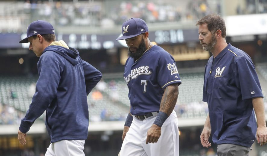 Milwaukee Brewers' Eric Thames leaves the game with manager Craig Counsell and a trainer during the eighth inning of a baseball game against the Cincinnati Reds Wednesday, April 26, 2017, in Milwaukee. (AP Photo/Morry Gash)