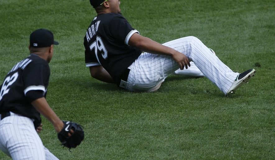 Chicago White Sox first baseman Jose Abreu, top, reacts after making an error hit by Kansas City Royals' Cheslor Cuthbert during the fifth inning of a baseball game, Wednesday, April 26, 2017, in Chicago. (AP Photo/Nam Y. Huh)