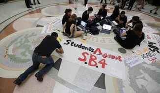 "Students gather in the Rotunda at the Texas Capitol to oppose SB4, an anti-""sanctuary cities"" bill that already cleared the Texas Senate and seeks to jail sheriffs and other officials who refuse to help enforce federal immigration law, as the Texas House prepares to debate the bill, Wednesday, April 26, 2017, in Austin, Texas.  Many sheriffs and police chiefs in heavily Democratic areas warn that it will make their jobs harder if immigrant communities, including crime victims and witnesses,  become afraid of police.  (AP Photo/Eric Gay)"